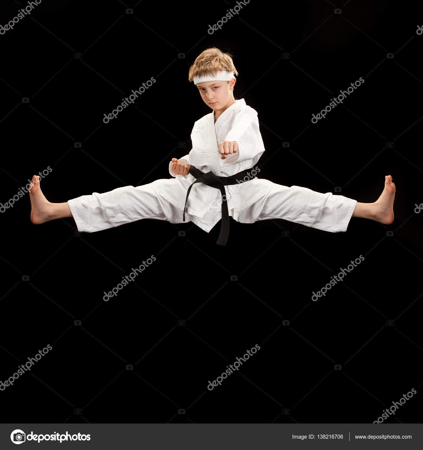 black belt karate kid fly kick isolated on black � stock