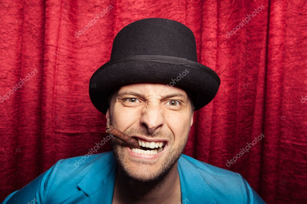 Caucasian sad man with party hat and cigar on red background