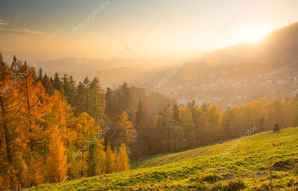 autumn landscape with town at sunset