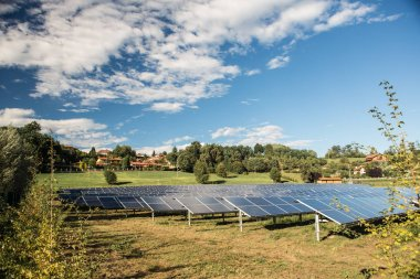 solar panel electricity central field in sunny day with blue sky and clouds
