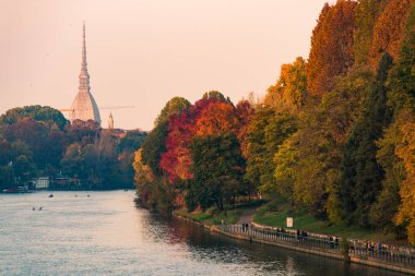 po river in turin city with mole antonelliana and people walking in part