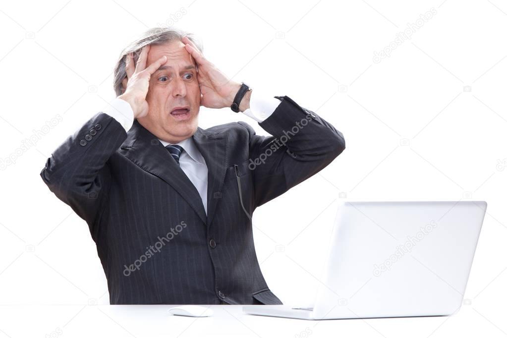 Surprised senior businessman isolated on white using laptop
