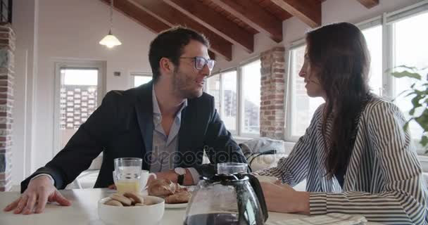 young caucasian couple in love talking while having italian breakfast and american coffee indoor in modern industrial house.4k handheld video shot