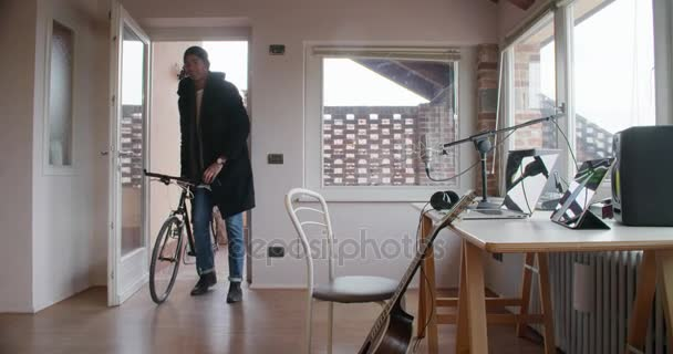 black man creative musician coming back by bike to home recording studio and get to work indoor in modern industrial house. 4k handheld video shot