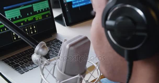 fekete férfi kreatív zenész home stúdióban játszik, ének és gitár notebook tablet és mikrofonnal beltéri felvétel modern ipari házban működik. 4k kézi hát-videóval
