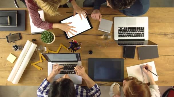 Top overhead view people group using tablet on a design project idea. Creative modern business team work meeting an at agency office. 4k indoor technology video