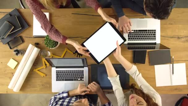 Top overhead view people group using and sharing tablet on a design project idea. Creative modern business team work meeting an at agency office. 4k indoor technology video