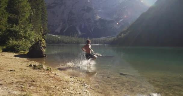 muž běží a potápění do divoké sunny jasné jezero