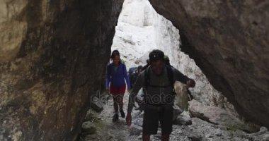 Friends walking along hiking trail rocky canyon path