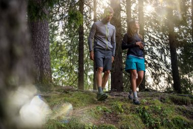 Man and woman walking in forest woods with sun flare light