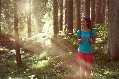 Happy woman with backpack walking on hiking trail path in forest woods during sunny day.Group of friends people summer adventure journey in mountain nature outdoors.Travel exploring Alps,Dolomites