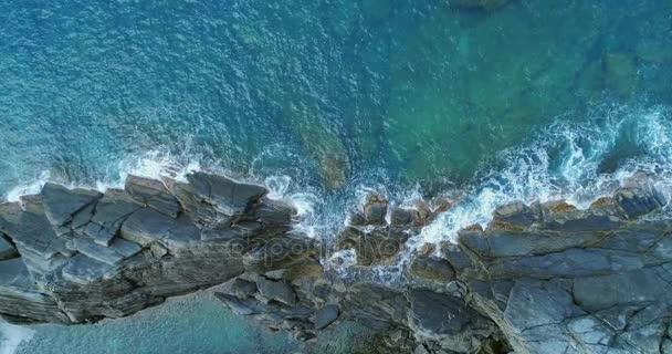 rezsi légifelvételek óceán Földközi-tenger hullámai és a sziklás parton beach partján összeomlik. Napos idő. 4k lassú mozgás 60 p felülnézet drone videóval