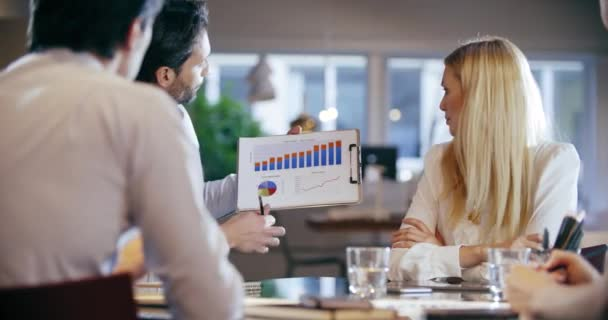 Corporate business team work meeting at office.Four caucasian businessman and businesswoman people group talking strategy together.Collaboration, growing, success concept using chart. 4k video