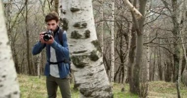 Man in woods looking and shoot photos in camera.Following side.Real people Millennial traveller backpacker adult male photographer walking on rural field to shoot photographs in autumn season.4k video