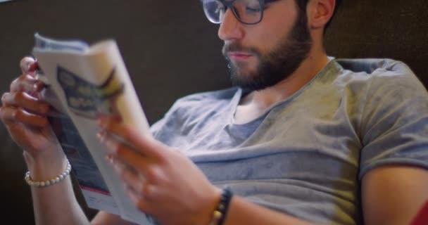 Mladý muž tisícileté relaxační čtení časopisu noviny doma v neformální oblékání. 4k video