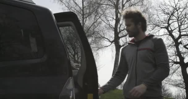 Muž, otevření off road nebo Suv čtyři kola jízdy vozidla kufru. Pár lidí v lásce podzimní venkovní výlet v přírodě. Na podzim slunečný den. 4 k video zpomaleně