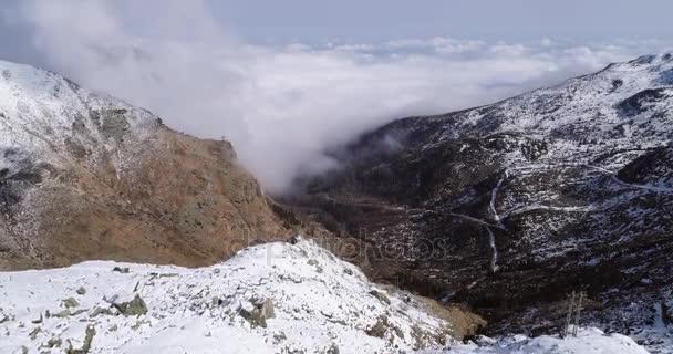 letecký létání, pohybující se vpřed přes zasněžený horský hřeben údolí s mraky a slunce zřizovatel. Venkovní sníh alpské přírody stvol v zimě. 4 k drone letu o shot