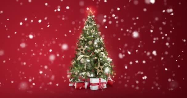 Opakování světla zdobené vánoční strom s dárkové krabičky na červeném pozadí a sněhové vločky padající s textem prostor umístit logo nebo kopírovat. Abstraktní vánoční přítomné přání. 4 k videa bezešvé smyčka