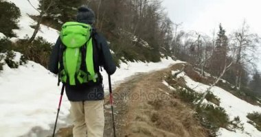 Hiker man with backpack walking on snowy trail path.Following behind.Real backpacker people adult hiking or trekking in autumn or winter in wild mountain outdoors nature,bad foggy weather.4k video