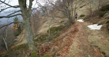 Athlete man running through snowy path.Following front.Real people adult trail runner sport training in autumn or winter in wild mountain outdoors nature, bad foggy weather.4k video