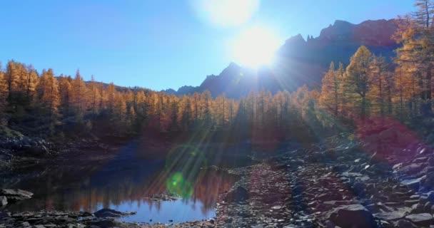 dopředné antény přes alpské horské údolí jezero a oranžové modřín Les lesy slunečný podzim. Stvol venkovní barevné přírody Alpách divoké spadají establisher.4k hukot let založení shot