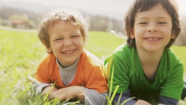 Šťastné děti s úsměvem zblízka portrét. Dvě děti bratra, smát a hrát zároveň ležel travní luční ve venkovní slunečný den. Rodinné syn chlapci v nature.video záběry