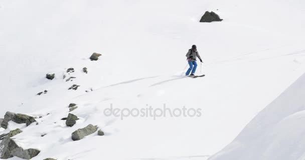 Muž freeride lyžování po zasněžené hory ridge v slunečný den. Horolezecká činnost ski. Lyžař lidí zimní snow sport v horské přírodě. Čelní pohled. Slow motion 60p 4 k videa