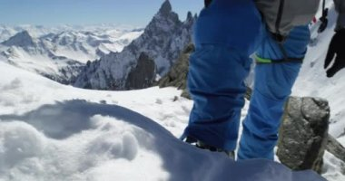 Climber mountaineer man using ice axe near snowy mount top in sunny day.Mountaineering ski activity. Skier people winter snow sport in alpine mountain outdoor.Back view.Slow motion 60p 4k video