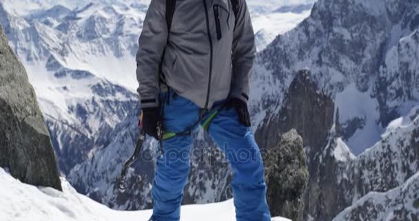 Horolezec horolezec muž dosáhl vrcholu zasněžené hory s cepín v slunečný den. Horolezecká činnost ski. Lyžař lidí zimní snow sport v horské přírodě. Čelní pohled. Slow motion 60p 4 k videa