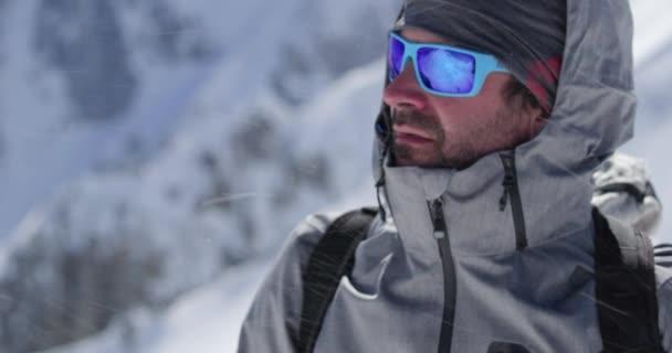 Horolezec horolezec Portrét muže na vrcholu zasněžené hory v slunečný den. Horolezecká činnost ski. Lyžař lidí zimní snow sport v horské přírodě. Boční pohled. Slow motion 60p 4 k videa