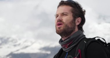 Detail of man face panting, resting and looking away.Mountaineering ski activity. Skier people winter sport in alpine mountain outdoor.Slow motion 60p 4k video