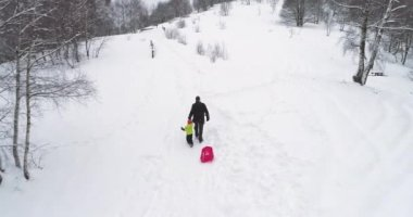 Winter aerial  follow father pulling red bobsled on snowy rise with child.Dad, son or daughter, bobsleigh on snow.Family people have fun together outdoors.4k drone flight video