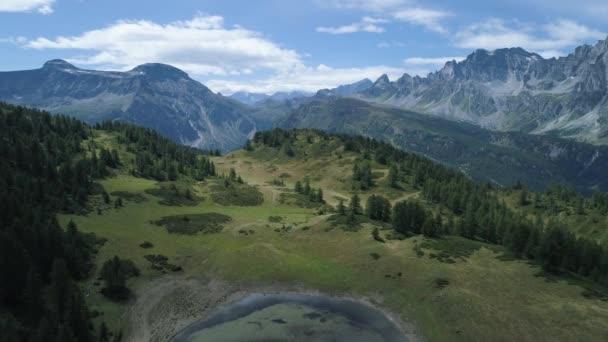 letecký vpřed modré alpské jezero odhalující lesní údolí v slunné léto s mraky. Evropa Alpy venku Zelená příroda stvol hory divoké letecké establisher.4k hukot založení shot