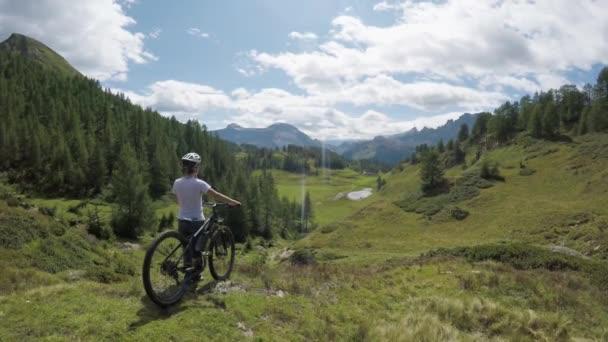 POV vpřed na kopce a lesy lesní s horský cyklista žena hledá panorama krajiny s mtb elektrokol v létě venku. Wanderlust aktivní sport cestování lidí. Alps divoké nature.4k hukot video