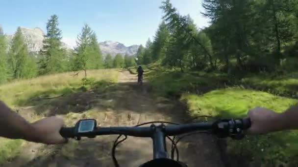 POV muž na koni e kolo po přítele žena. MTB akce cyklista zkoumání společně trail cestě nedaleko lesa. Elektrické kolo aktivních lidí sport cestování dovolená v Alpách Itálie venku v summer.4k video