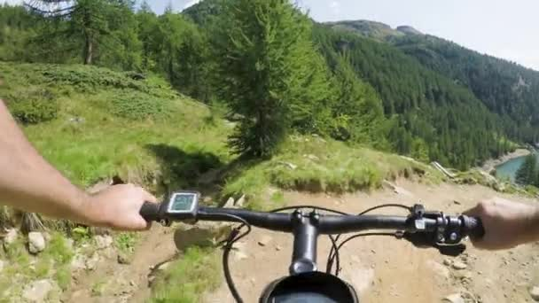 POV man riding e-bike on downhill near lake Mtb action cyclist exploring  trail path near mountains Electrical bike active people sport travel  vacation in Europe Italy Alps outdoors in summer 4k video
