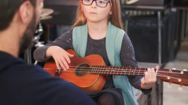 Apa gitárt és ukulelét tanít a lányának.Kislány otthon tanul gitárt.Közel.Ukulele osztály otthon. Gyermek gitárt tanul az apjától.