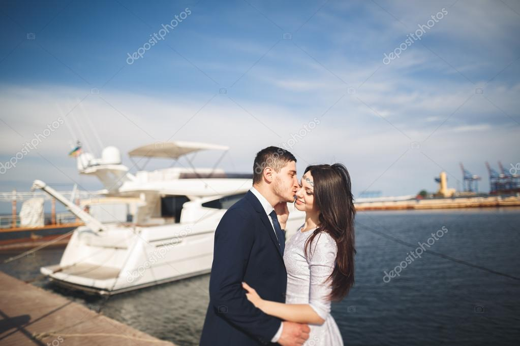 Happy wedding couple hugging near new yacht