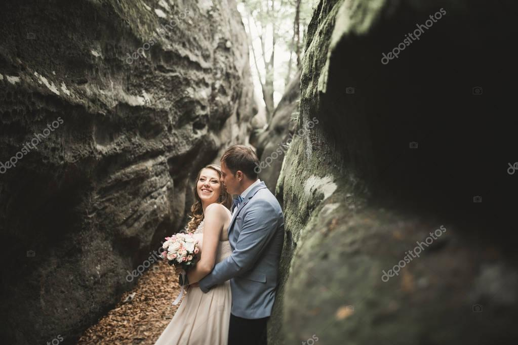 Gorgeous wedding couple kissing and hugging in forest with big rocks