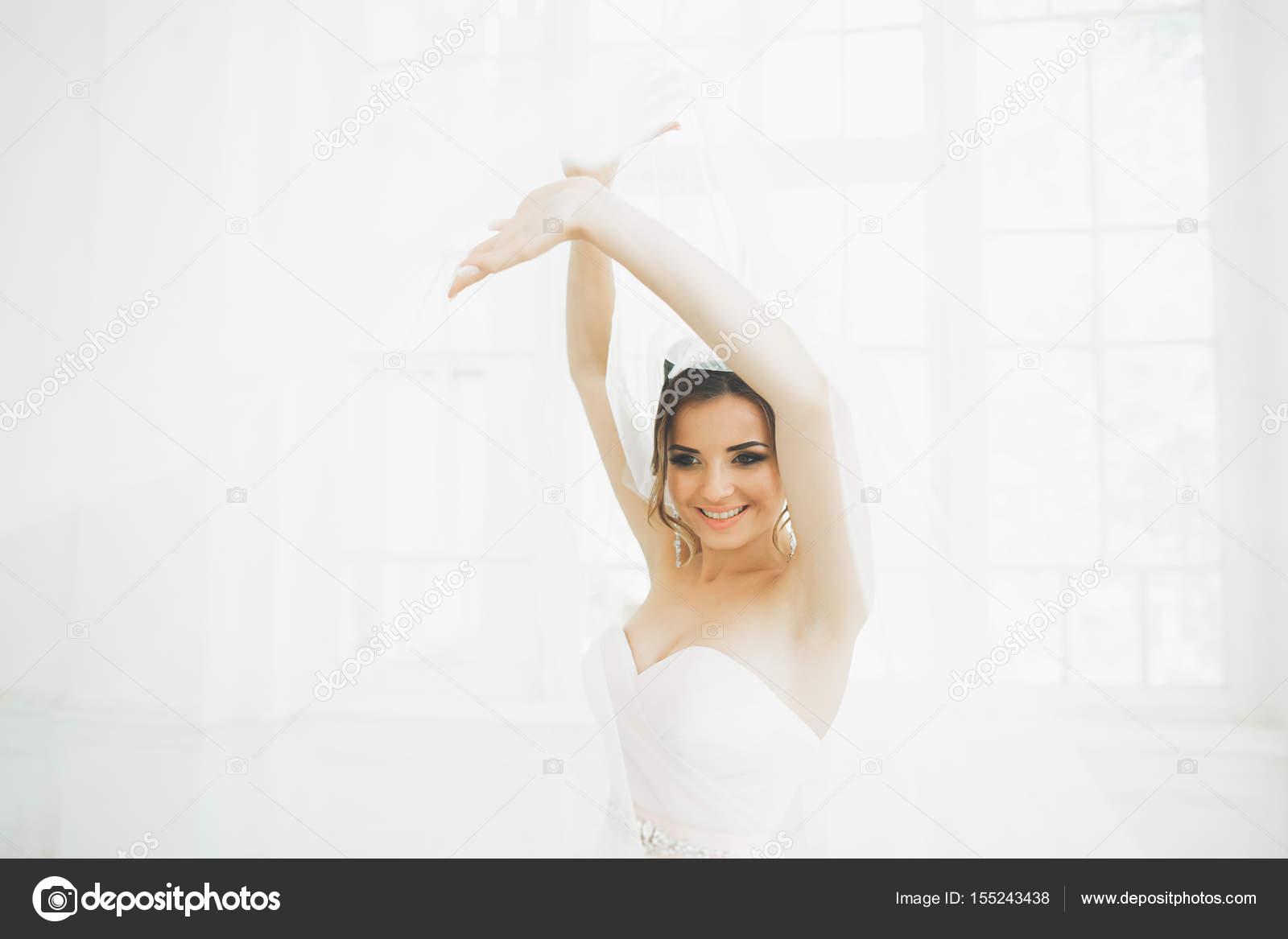 9f824fc51841 Vackra brud i brudklänning med lång hel kjol, vit bakgrund, dansar och ler —