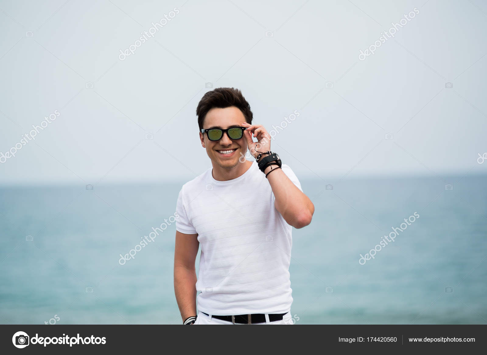 713564557799 Portrait of young man in sunglasses smiling on the beach — Stock Photo