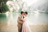 Gorgeous happy couple standing close to each other and looking in eyes near a beautiful lake in the mountains