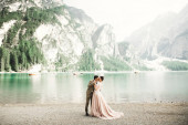 Young couple near a beautiful lake in the mountains. Lovers love one another close and smile