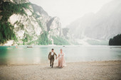 Young couple near lake Lago Di Braies, Italy. Holding hands at the stone at lake