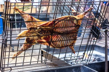 Appetizing grilled lamb on the spit. Roasted pig on traditional barbecue. Roasting barbecue is prepared of a ram pig baked pork meat Street food Whole carcass pig roasting on the grill over charcoal.