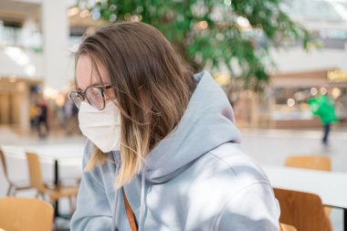 Woman in medical face mask siting in mall close up portrait. Corona virus infection protection