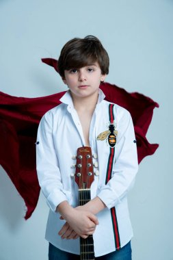 boy posing with acoustic guitar on photo studio on gray background