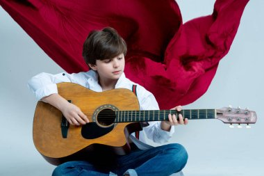 boy kid playing on acoustic guitar on photo studio