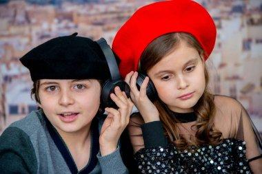 kids girl and boy listening music on headphones on romantic background