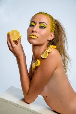 beautiful girl with yellow hair and a slice of lemon